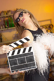 Blonde Caucasian movie star posing on film set behind director s clapper uid 1356093