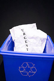 Crumpled piece of paper with the word urgent in blue recycling box uid 1171896