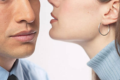 Woman whispering secret into man s ear uid 1271501